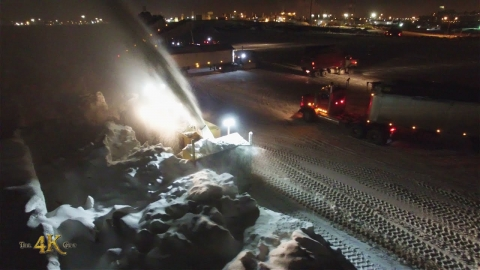 Snowplow video 2 - Snow dump with blower and trucks at night viewed...